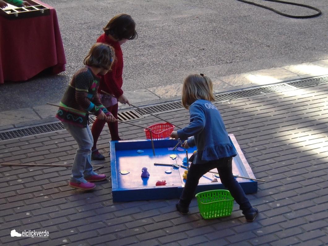 Tres niñas, tratando de 'pescar' unos juguetes.