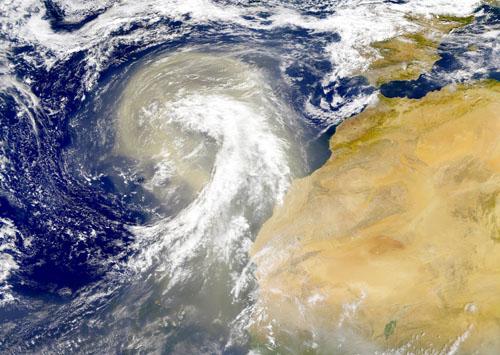 Imagen de satélite de una gran masa de polvo desplazándose hacia el oeste sobre las Islas Canarias, con un tamaño equivalente al de la península Ibérica (margen superior derecho). Imagen: NASA Earth Observatory / CSIC